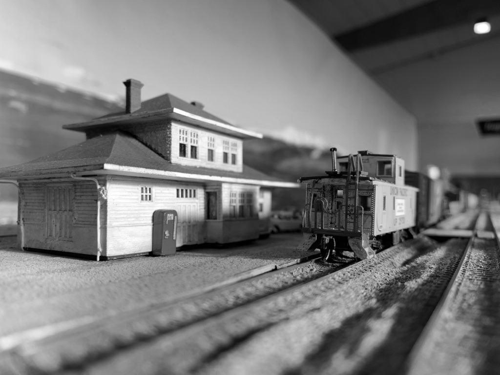 Black and white photo of the model of the cascade depot with a UP caboose in front